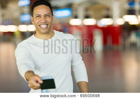handsome mature man handing over air ticket at check in counter