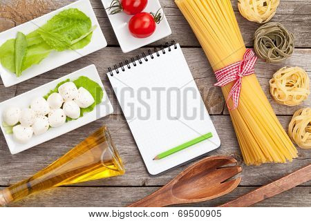 Tomatoes, mozzarella, pasta and green salad leaves on wooden table background with notepad for copy space