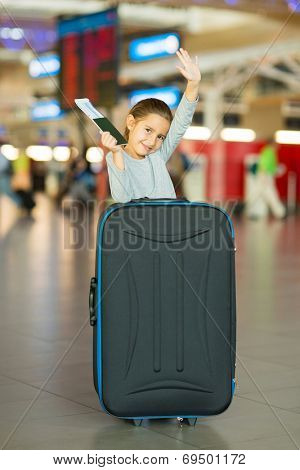 pretty little girl waving goodbye at airport