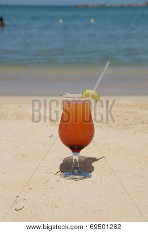 Cold orange cocktail in sand on beach