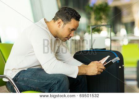 good looking mid age man using smart phone at airport