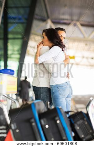 sad young couple say goodbye at airport