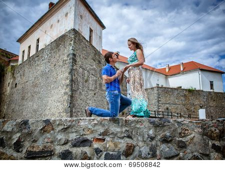 guy proposing marriage to the girlfriend against the old lock