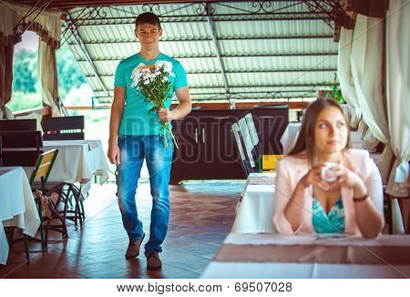 Proposal. ��oung couple in an open-air cafe
