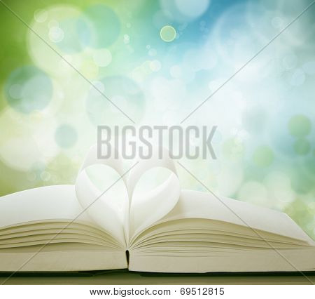 Pages of book in shape of love heart in front of blue green background