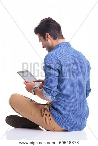side back view of a smiling young man working on a tablet pad computer on white background