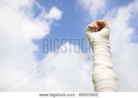 Raise Bandaged Arm  With Blue Sky Background