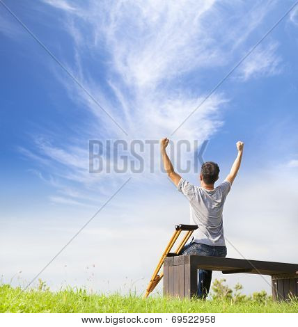 Injured Man Raise Hands And  Sitting On A Bench With Crutches