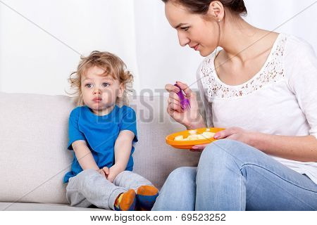 Mother Feeding Child On Couch