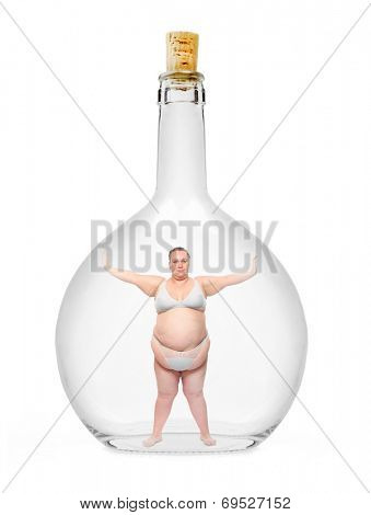 Overweight woman closed in a glass bottle. Nutrition problem and weight discrimination concept.