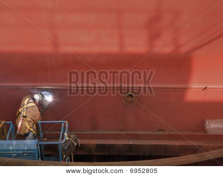 Welder In Man Lift Welding On Ship Hull