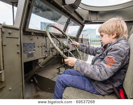 Kid At The Wheel Of A Military Vehicle