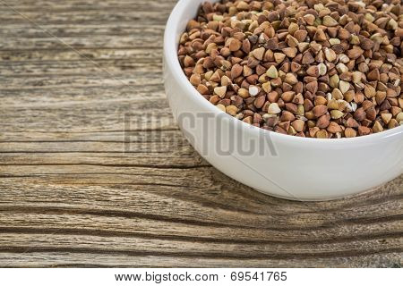 roasted buckwheat grain (kasha) in a small white bowl against grained wood