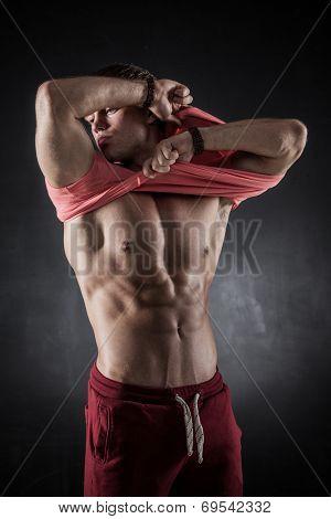 Brutal athletic man taking shirt off on dark background