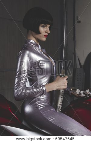 Danger, Beautiful brunette woman wearing latex mounted on a motorcycle with a modern design