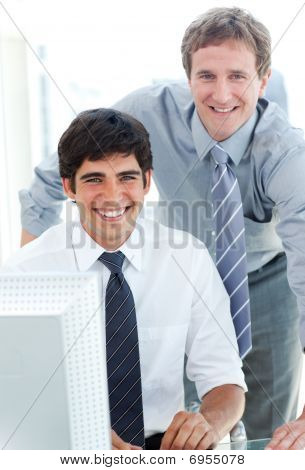 Two Male Executives Working At A Computer