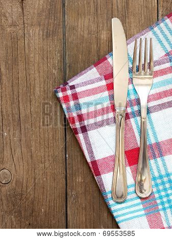 Fork And Knife On Kitchen Towel And Old Wooden Table