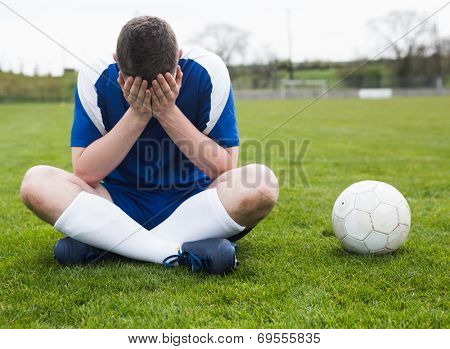 Disappointed football player in blue sitting on pitch after losing on a clear day