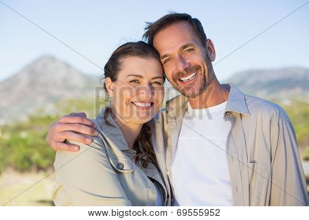 Hiking couple smiling at camera in the countryside on a sunny day