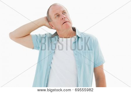 Thoughtful older man looking up on white background