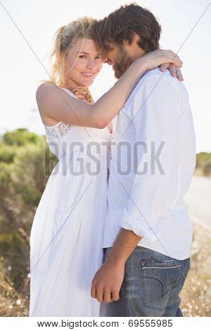 Attractive couple embracing by the road on a sunny day