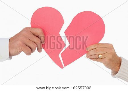 Couple holding a broken paper heart on white background