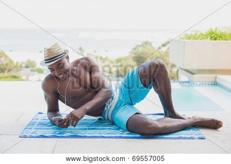 Handsome shirtless man listening to music poolside on a sunny day