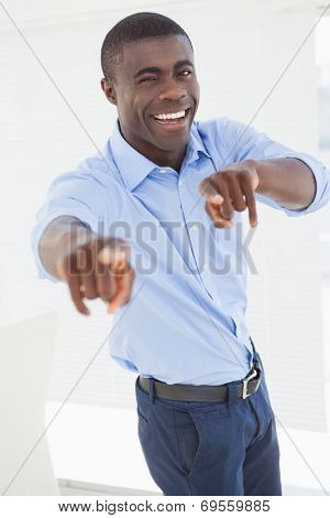 Happy businessman pointing at camera in his office