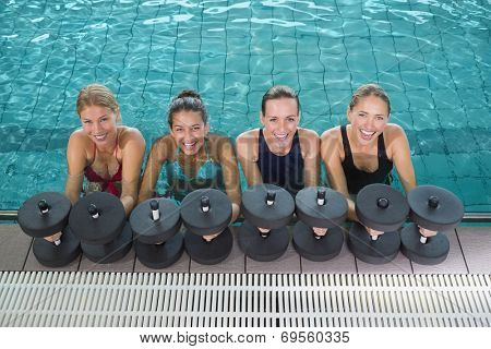 Female fitness class doing aqua aerobics with foam dumbbells in swimming pool at the leisure centre