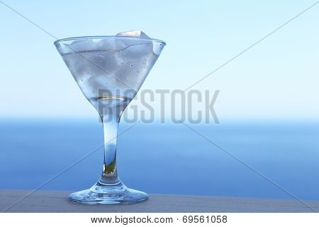 Cold cocktail with ice cubes and relaxing summer background