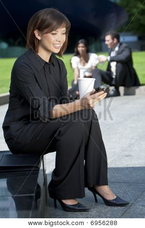 Beautiful Young Chinese Asian Woman Texting And Drinking Coffee