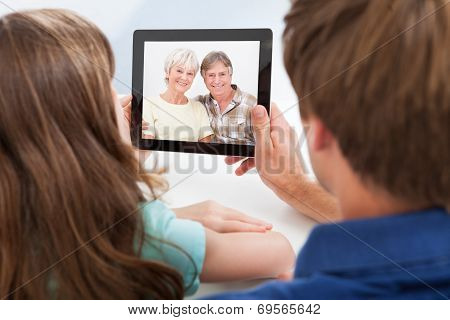 Daughter With Father Video Chatting On Digital Tablet