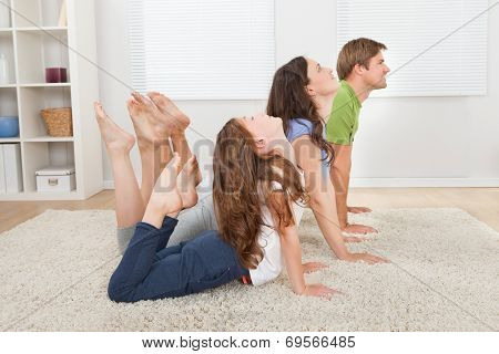 Active Family Doing Yoga At Home