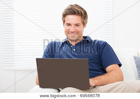 Man Using Laptop On Sofa At Home