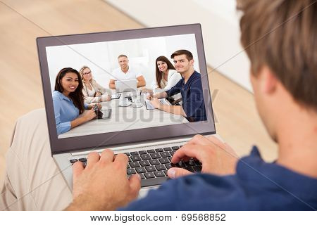 Man Attending Conference Meeting On Laptop At Home