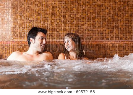 Beautiful couple doing a whirlpool bath in a spa