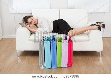 Businesswoman Sleeping On Sofa With Shopping Bags On Floor