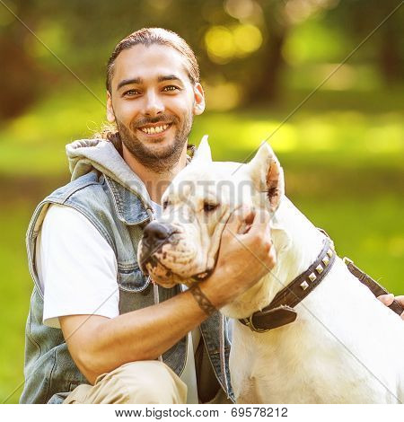Man And Dogo Argentino Walk In The Park.