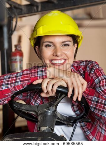 Portrait of happy female engineer wearing hardhat while leaning on steering wheel of forklift in workshop