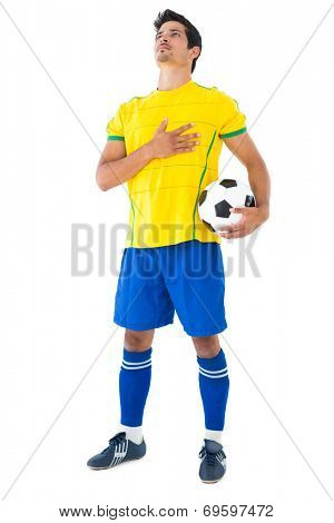 Football player in yellow with ball listening to anthem on white background