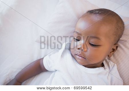 Adorable baby boy lying in his crib at home in the bedroom