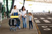 stock photo of trolley  - cheerful young family at airport with a trolley full of luggage  - JPG