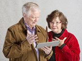 pic of overwhelming  - Overwhelmed senior man and woman holding tablet - JPG