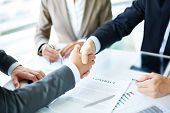 pic of trade  - Image of business partners handshaking over business objects on workplace - JPG
