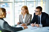stock photo of attention  - Two serious business partners listening attentively to young man at meeting in office - JPG