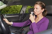 foto of sobriety  - Young woman in car blowing into breathalyzer - JPG
