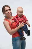 pic of fussy  - Portrait of young attractive mother holding her screaming toddler son being naughty and cranky, isolated on white ** Note: Soft Focus at 100%, best at smaller sizes - JPG