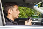 stock photo of blood drive  - Youg man in car looking at breathalyzer - JPG