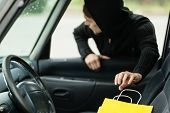 stock photo of delinquency  - Transportation crime and ownership concept - thief stealing shopping bag from the car