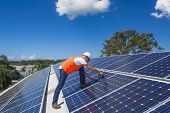 stock photo of roofs  - Young technician installing solar panels on factory roof - JPG